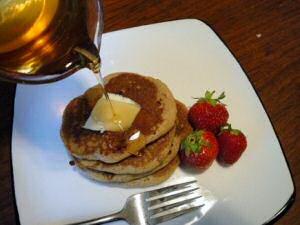 Boekweit pannenkoeken geserveerd met warme siroop, een klontje boter en verse aardbeien