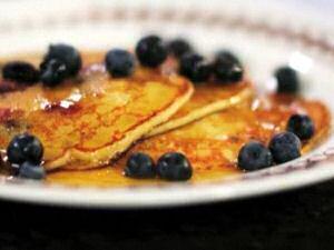 Een bord met enkele kleine, dikke pannenkoeken gebakken door Jeroen Meus, geserveerd met blauwe bosbessen en esdoornsiroop