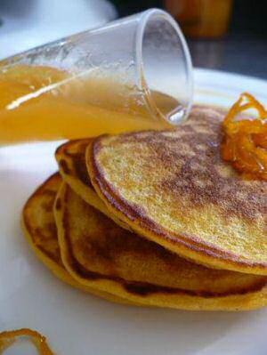 4 pompoenpannenkoeken op elkaar gestapeld geserveerd met zelfgemaakte sinaasappelsiroop